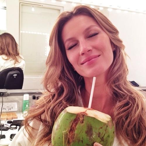 Giselle Bunchen si gode la sua acqua direttamente dalla fonte naturale del cocco verde.